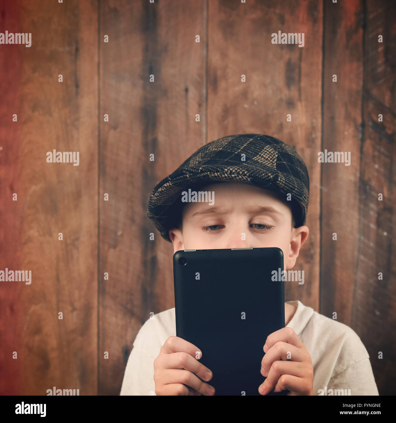 A boy is holding a technology tablet and reading a screen. The chikld is wearing a vintage cap with a wood background - Stock Image