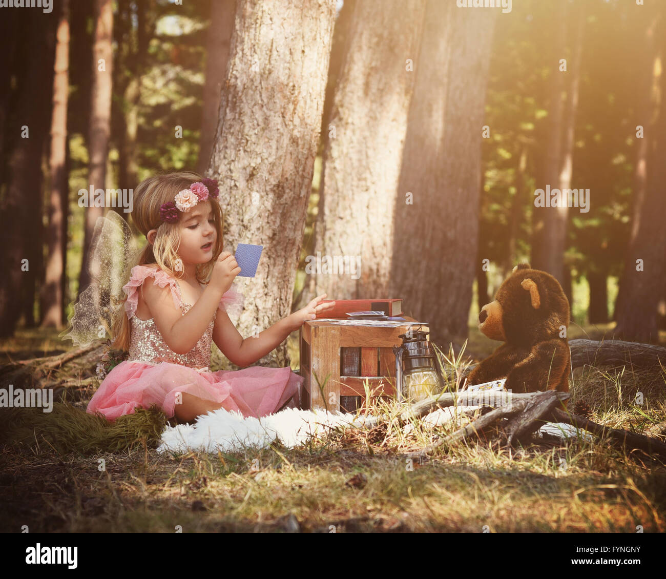 A little fairy girl is sitting in the woods playing a card game with a teddy bear for an imagination or fairy tale - Stock Image