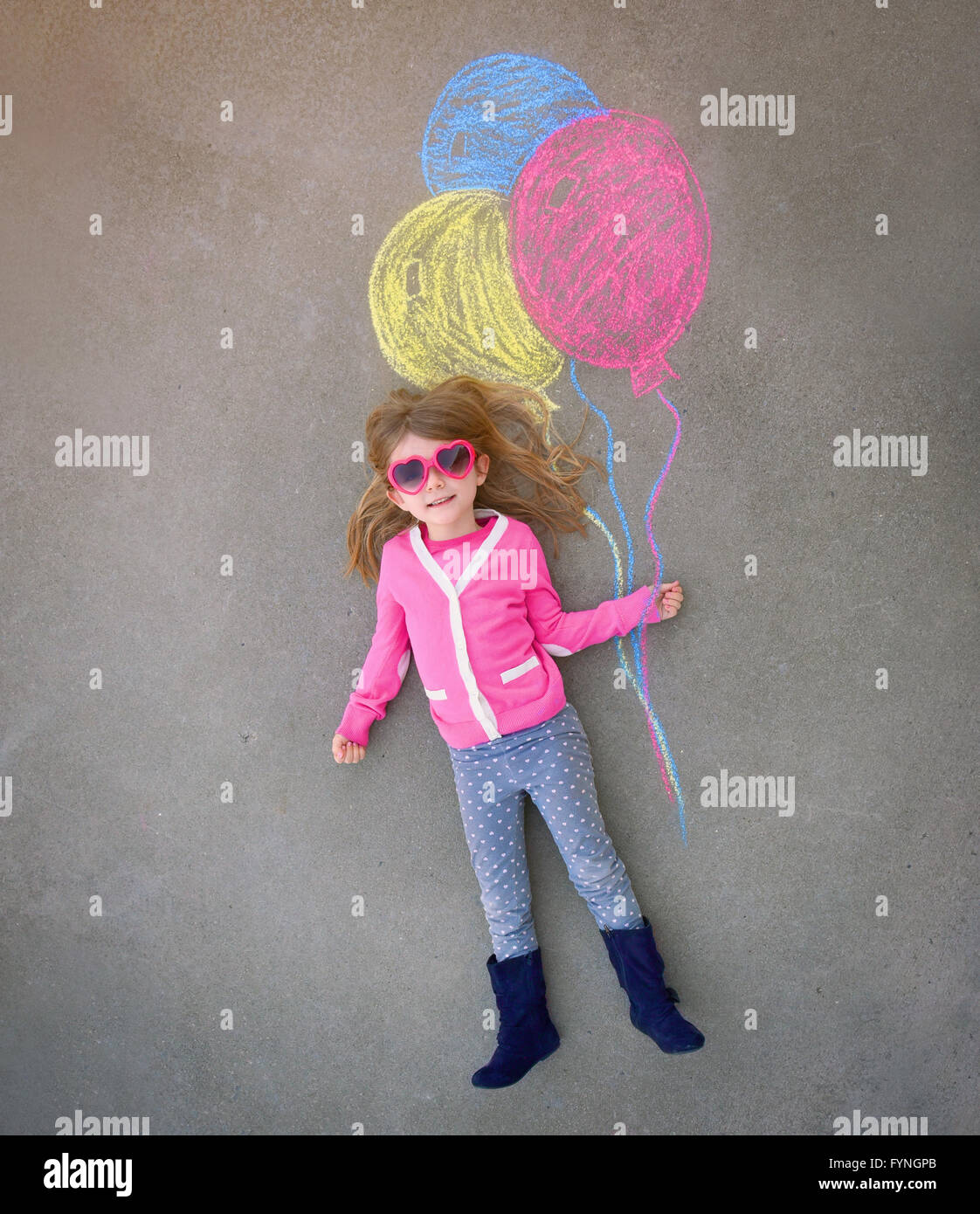 A cute little girl with sunglasses is holding creative chalk balloons drawn on the sidewalk cement for a imagination, - Stock Image