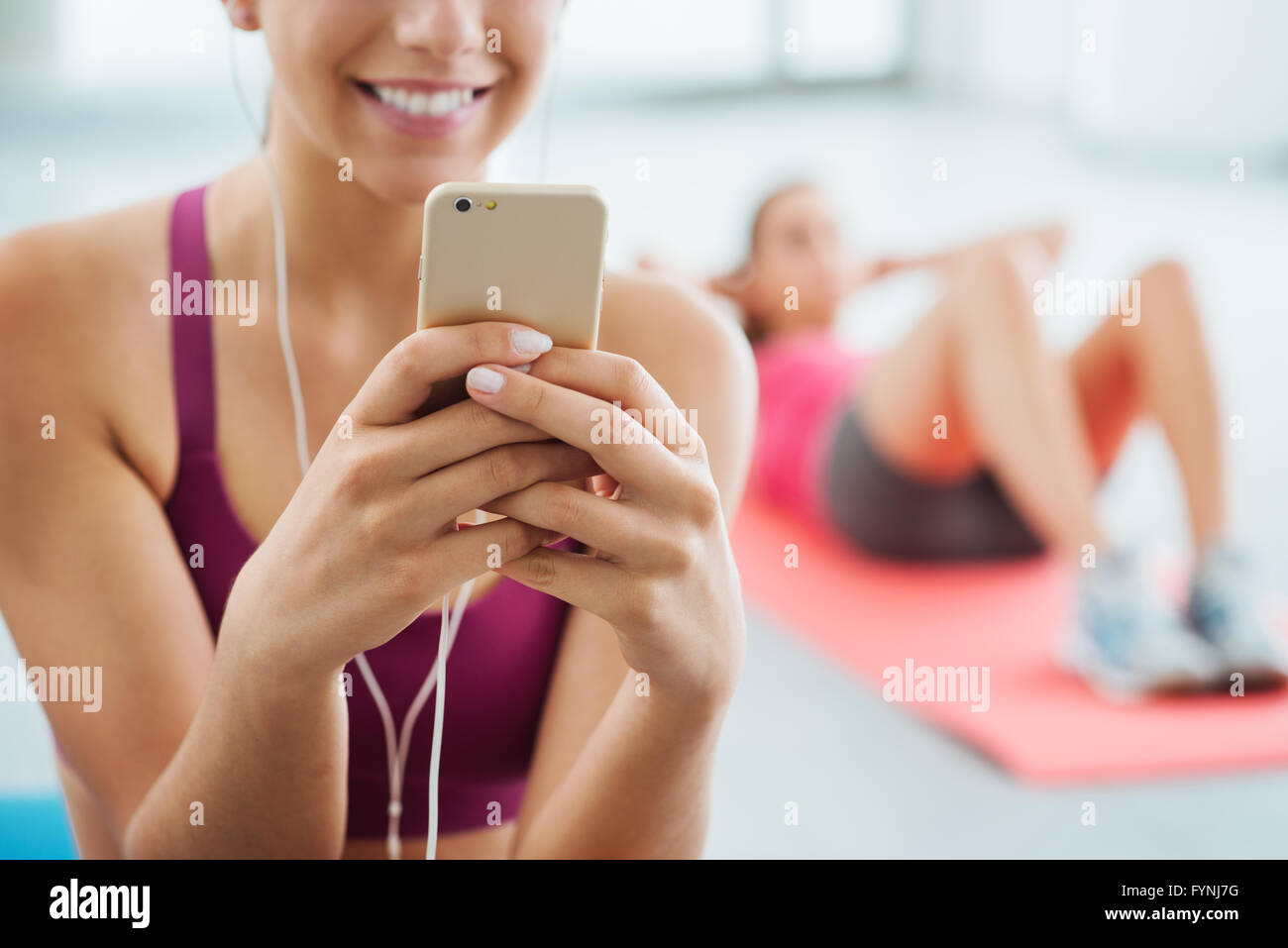 Young smiling woman at the gym relaxing and listening to music using a mobile phone and earphones - Stock Image