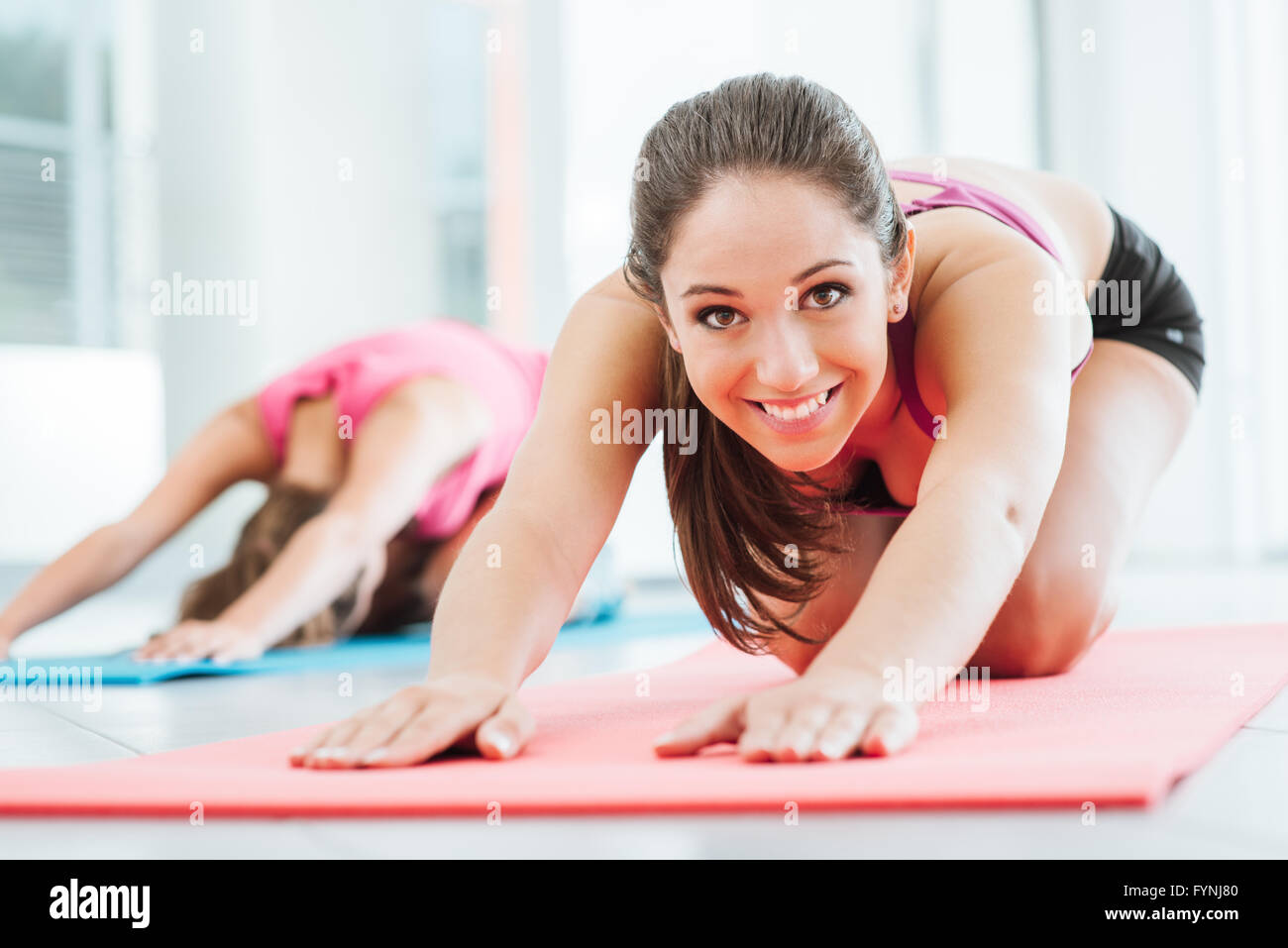 Girls at the gym doing stretching exercises on a mat, one is smiling at camera - Stock Image