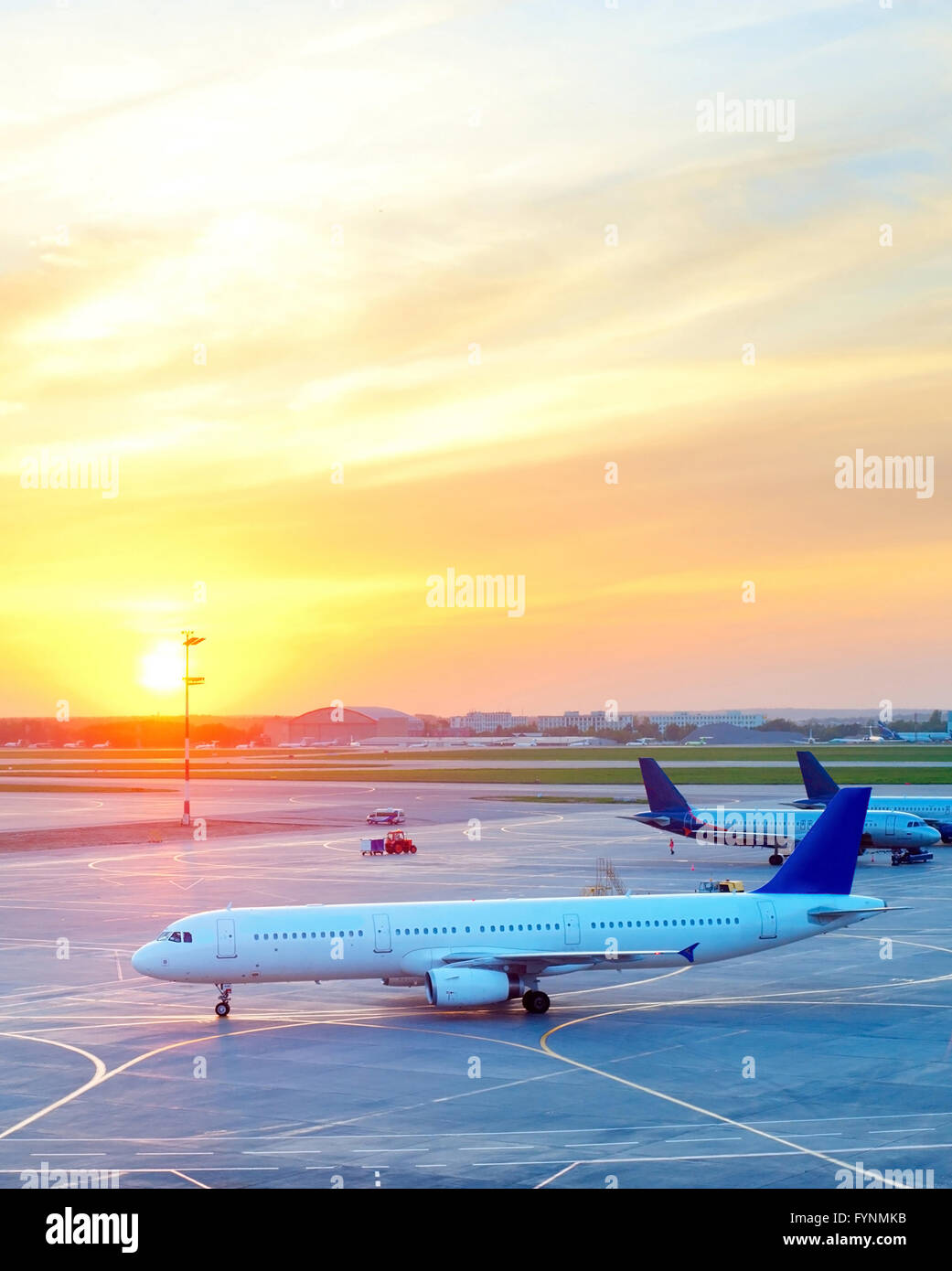 Planes at airport in the beautiful sunset - Stock Image