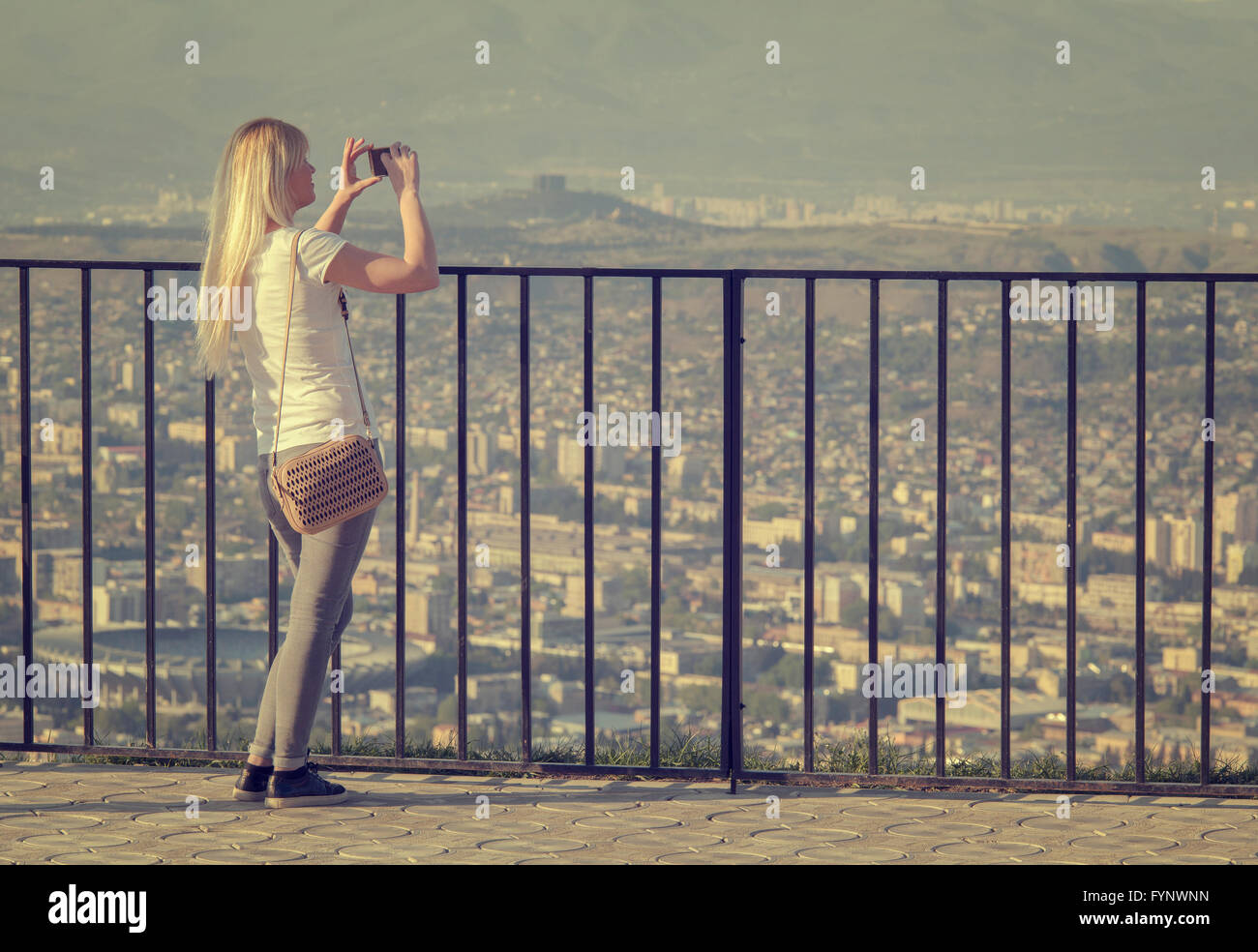 tourist photographing cityscapes with mobile phone - Stock Image