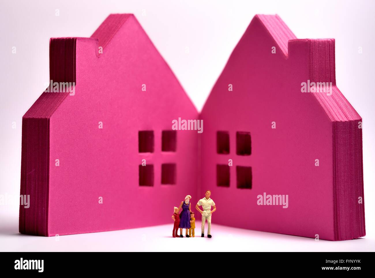 Pink post it notes in the shape of  houses with a miniature figurine family standing in front - Stock Image