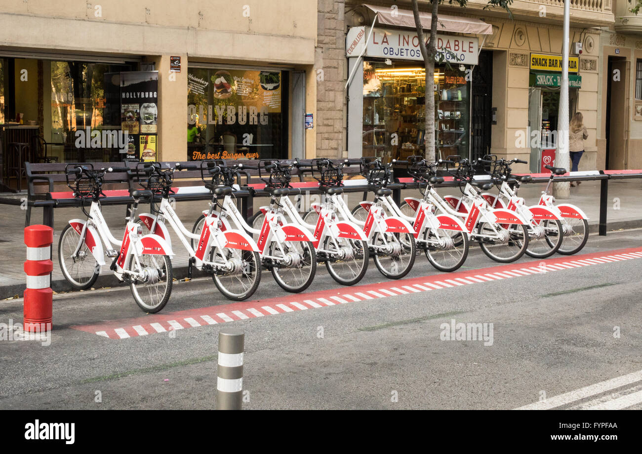 Row of bright red and white bikes in Barcelona - Stock Image