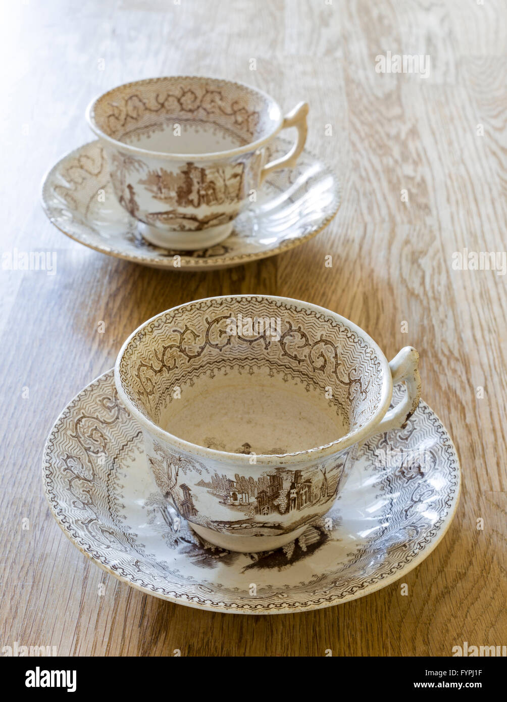 Two old antique porcelain coffee or tea cup and saucer on wooden table - Stock Image