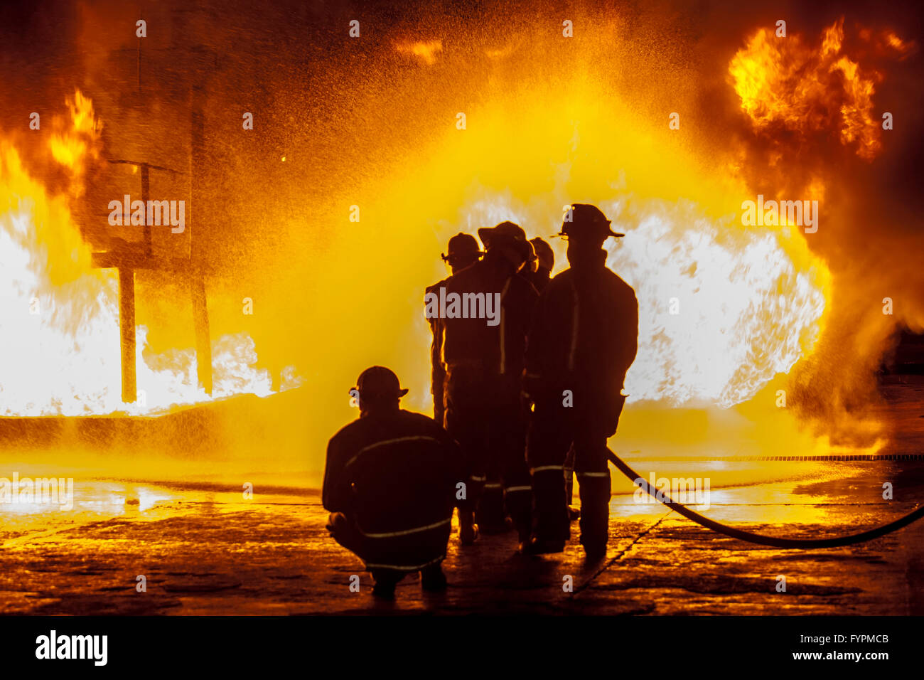 Firefighters spraying down burning structure - Stock Image