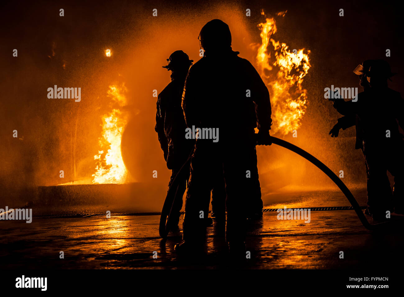 Firefighters standing in a line fighting a fire Stock Photo
