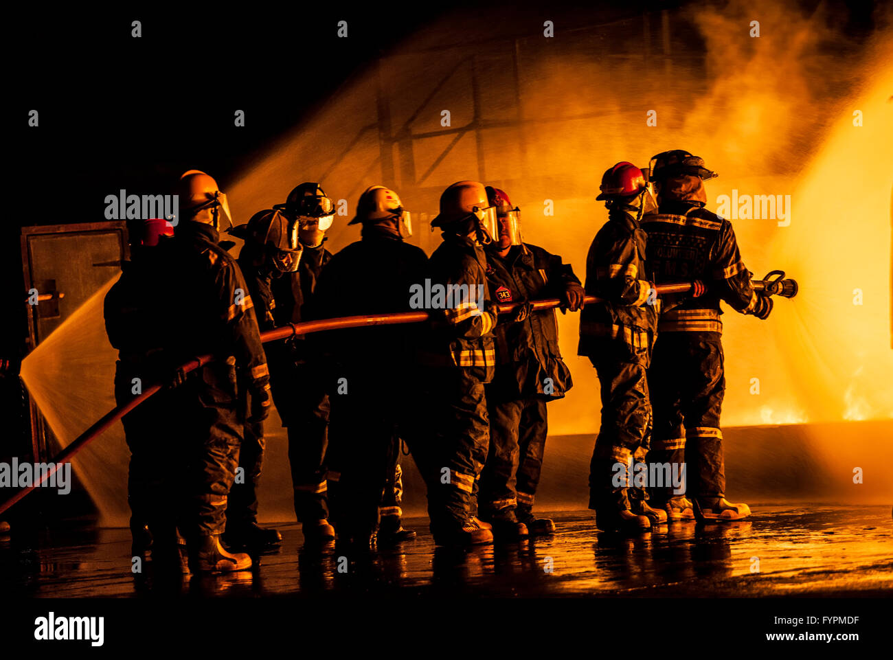Group of firefighters fighting a burning fire - Stock Image