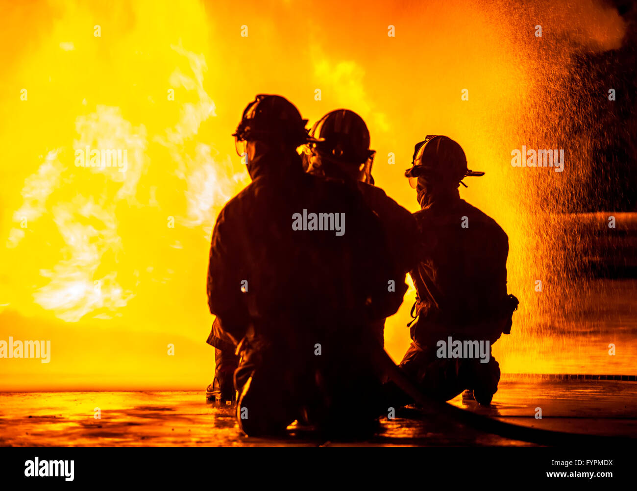 Three firefighters kneeling in front of fire Stock Photo
