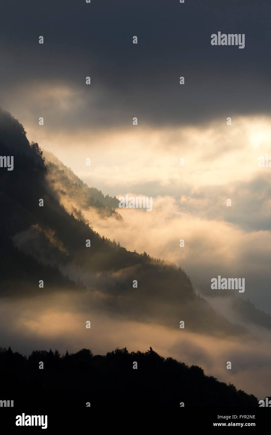 Fog on the mountainside above the Inn Valley, sun shining through clouds, Stans, Tyrol, Austria - Stock Image