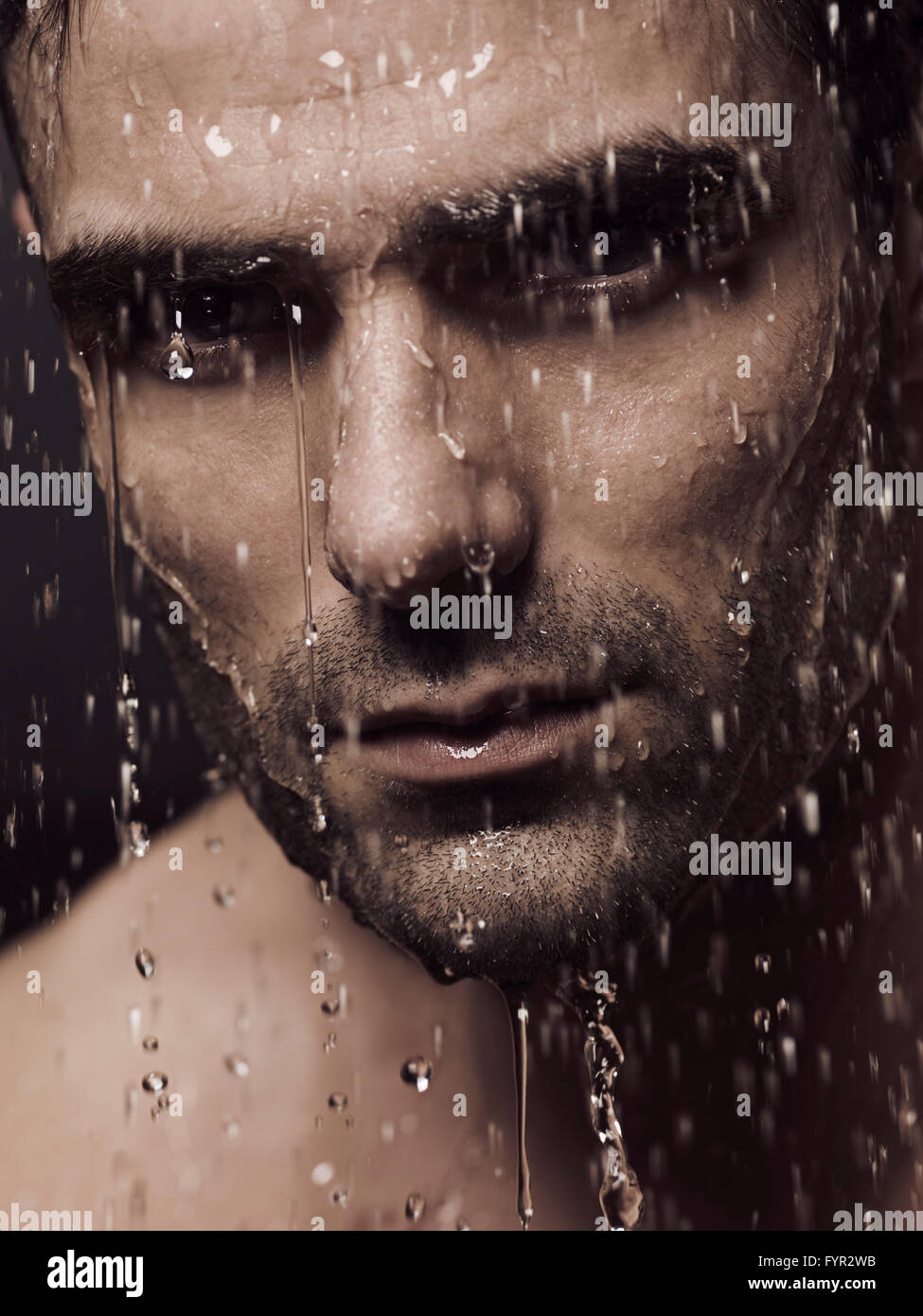 Water pouring from man's face, portrait - Stock Image