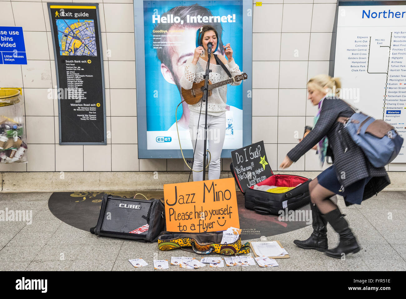 Jazz Mino sings and plays the ukulele as she busks for passengers passing through Waterloo underground station, - Stock Image