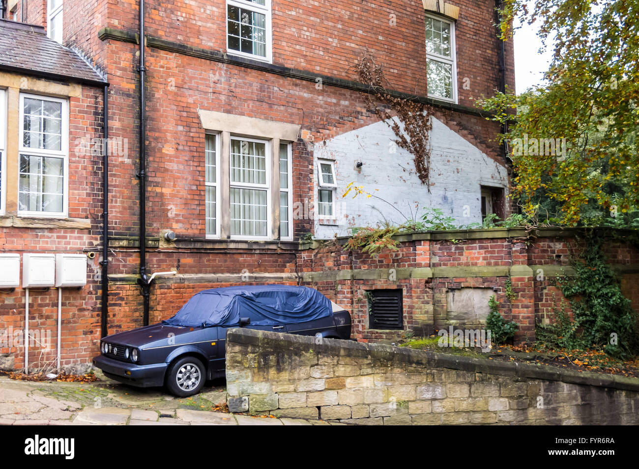 A blue VW Golf MK2 convertible hatchback car with a cover over it, parked next an old run down house in Durham City, - Stock Image