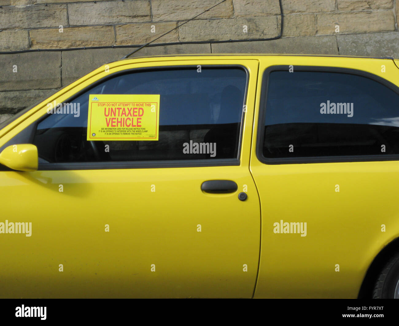 A Small Yellow Car With Dvla Untaxed Vehicle Notice In The Front