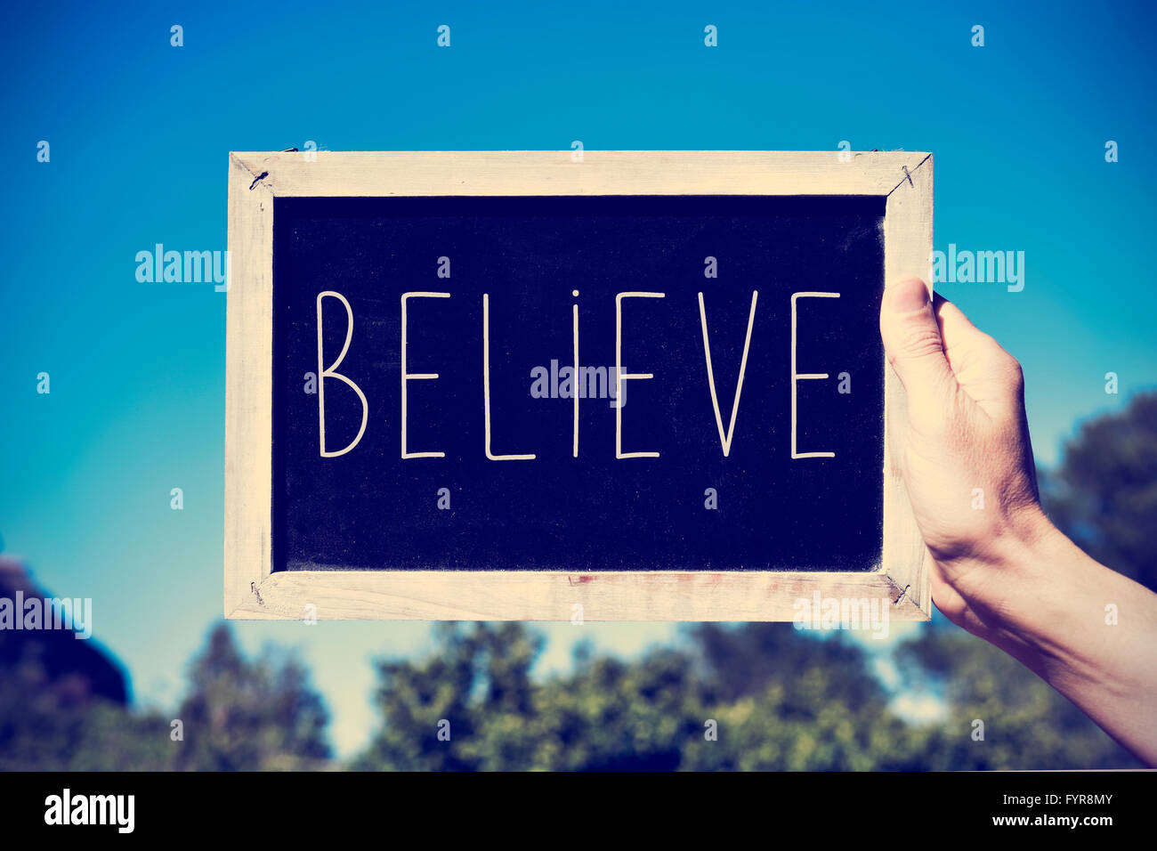 closeup of the hand of a young man holding a chalkboard with the text believe against the blue sky, with a retro - Stock Image