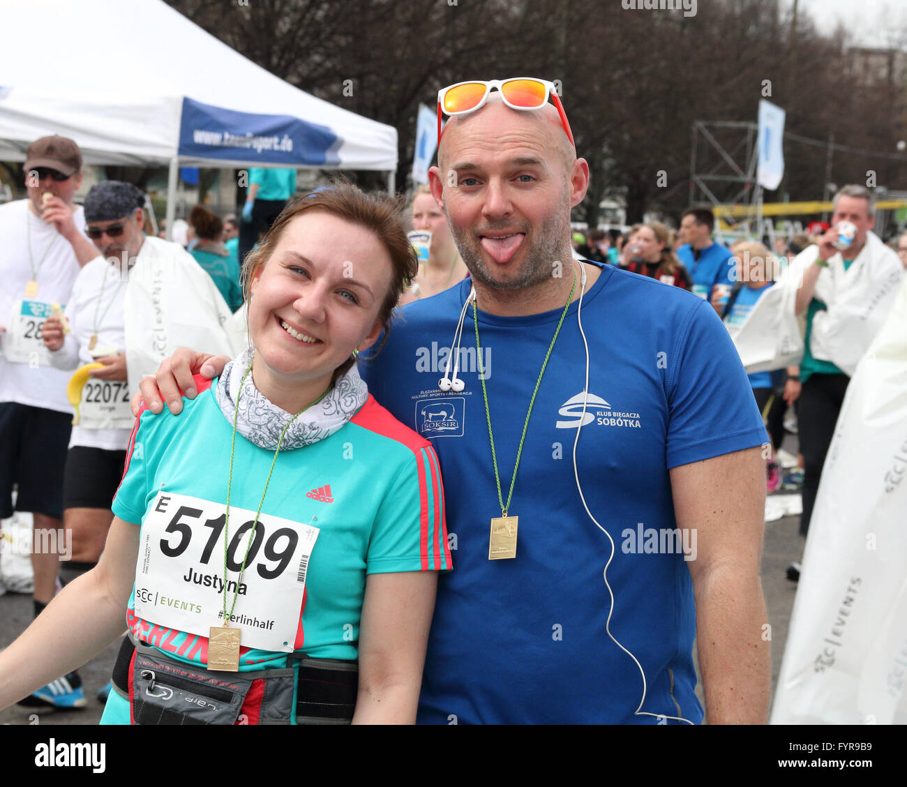 Man and woman wearing their medals after finishing the Berlin Half Marathon - Stock Image