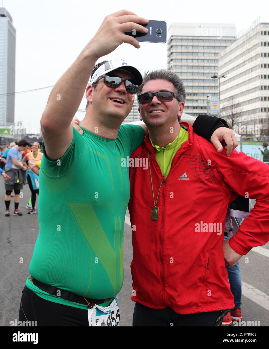 Two men with arms over each others shoulders taking a selfie at the end of the Berlin Half Marathon - Stock Image