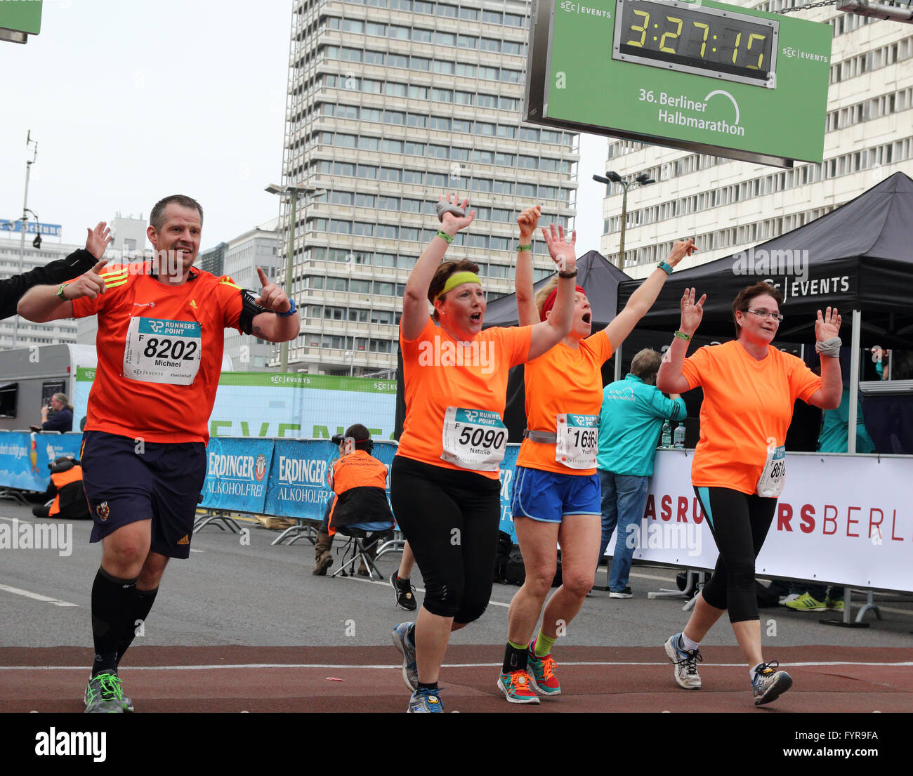 Three women and one man crossing the finish line of the Berlin Half Marathon with arms raised - Stock Image