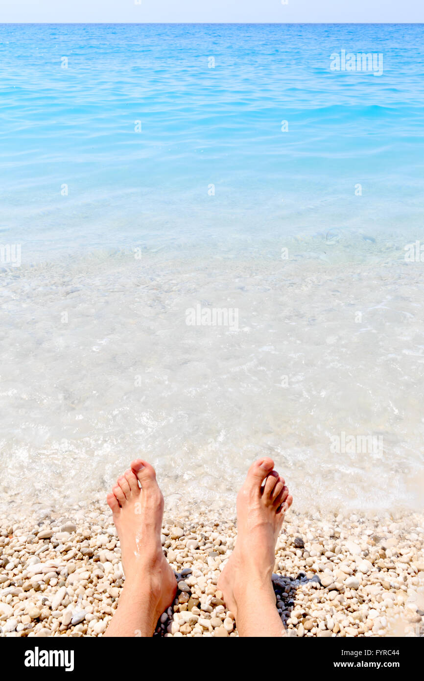 Beach holiday - male feet and summer sea - Stock Image