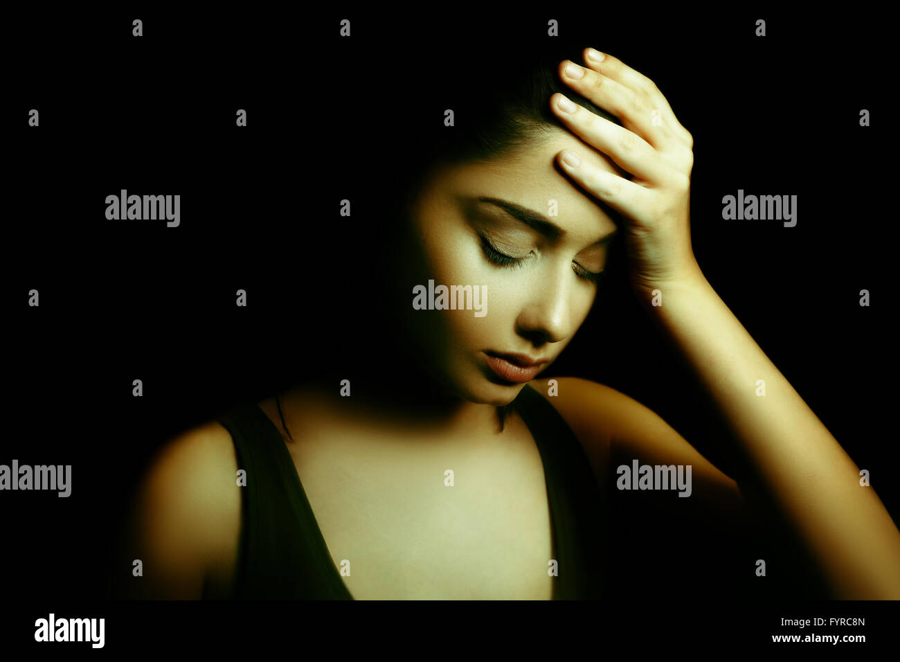 Depression Concept. Sad Young Woman with Face in the Dark - Stock Image