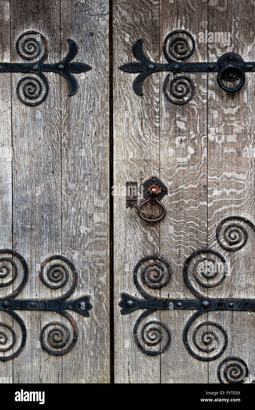 Old oak wooden door and ornate ironwork. Cotswolds, UK Stock Photo
