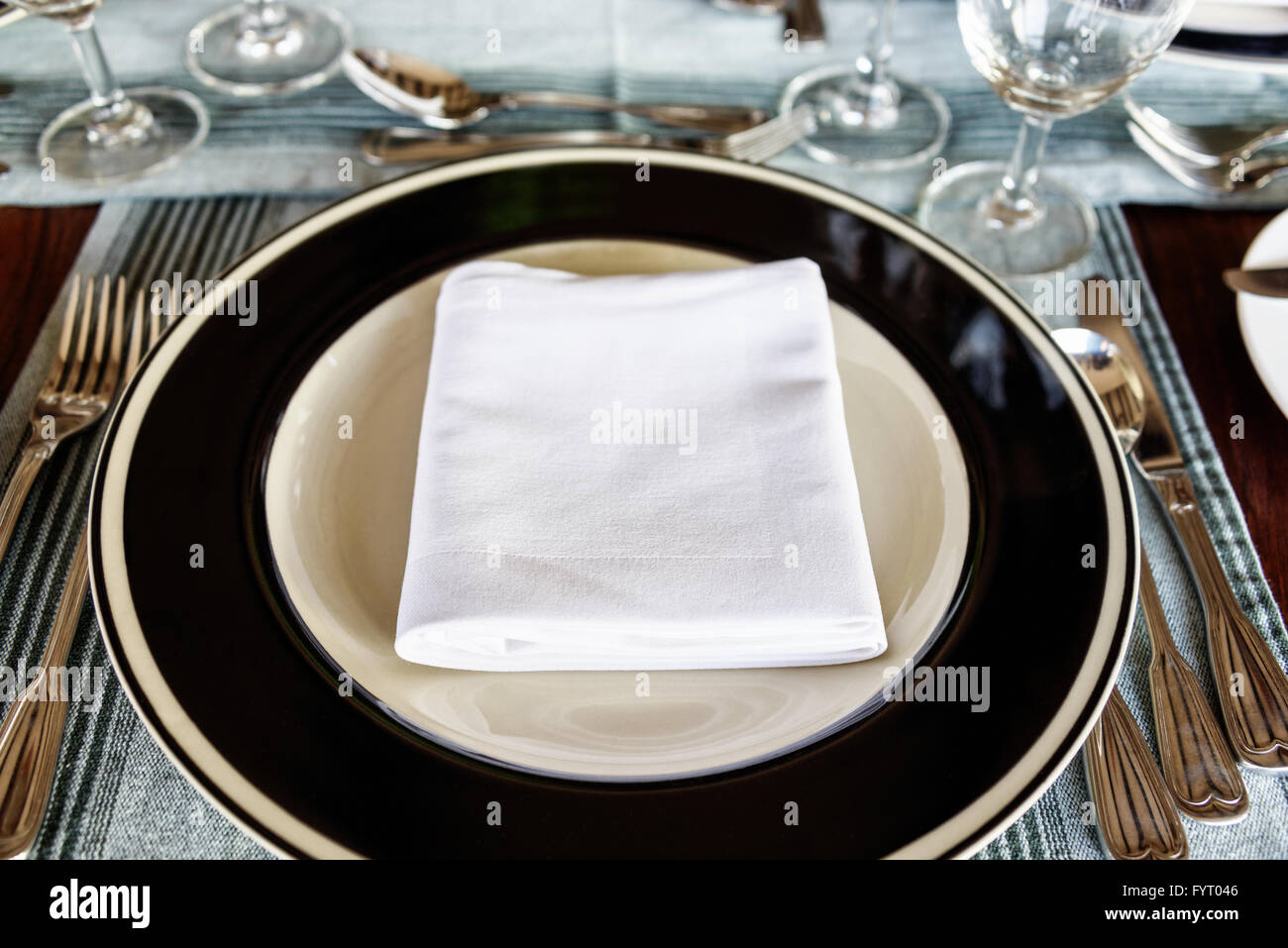 First person perspective view on neatly arranged dining table setting with folded napkin in middle of plate with utensils & First person perspective view on neatly arranged dining table ...