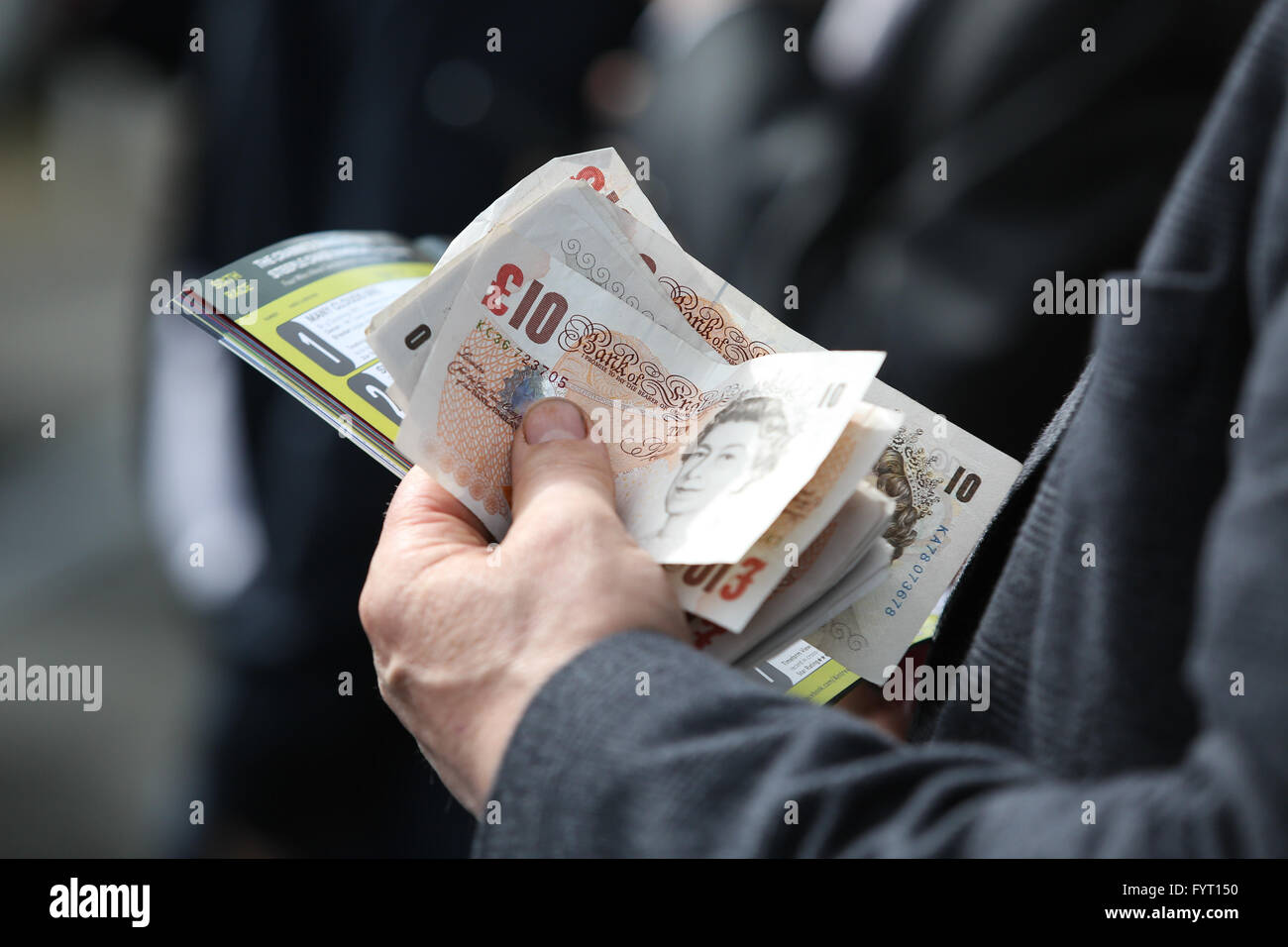 A man holds a wad of cash at the 2016 Grand National at AIntree Racecourse in Liverpool, UK. - Stock Image