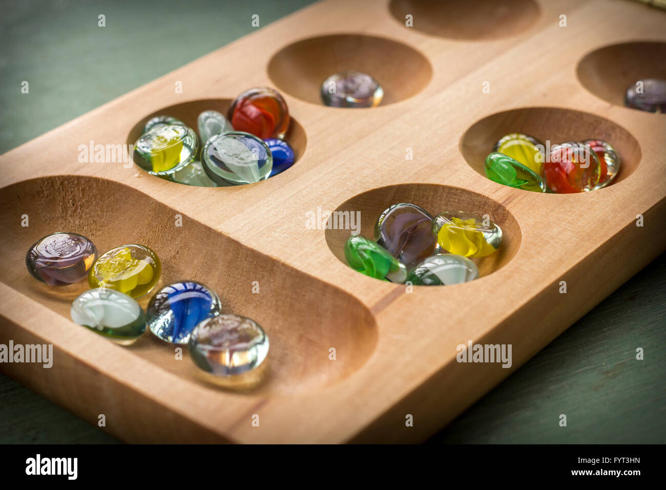 Traditional Mancala boardgame with glass pieces on wooden table - Stock Image