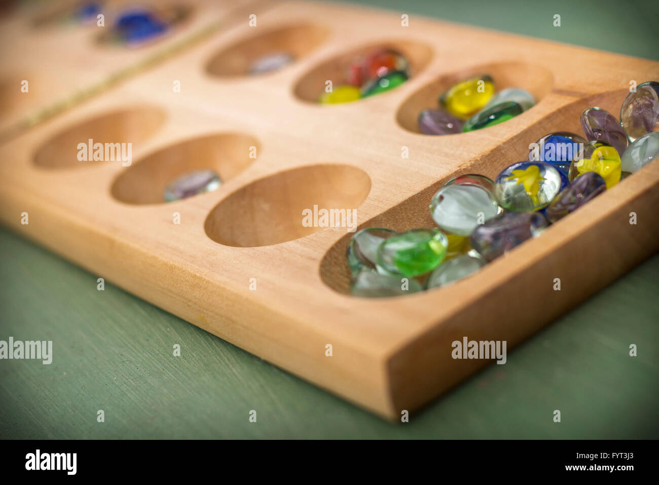 Traditional Mancala boardgame with glass pieces on wooden table Stock Photo