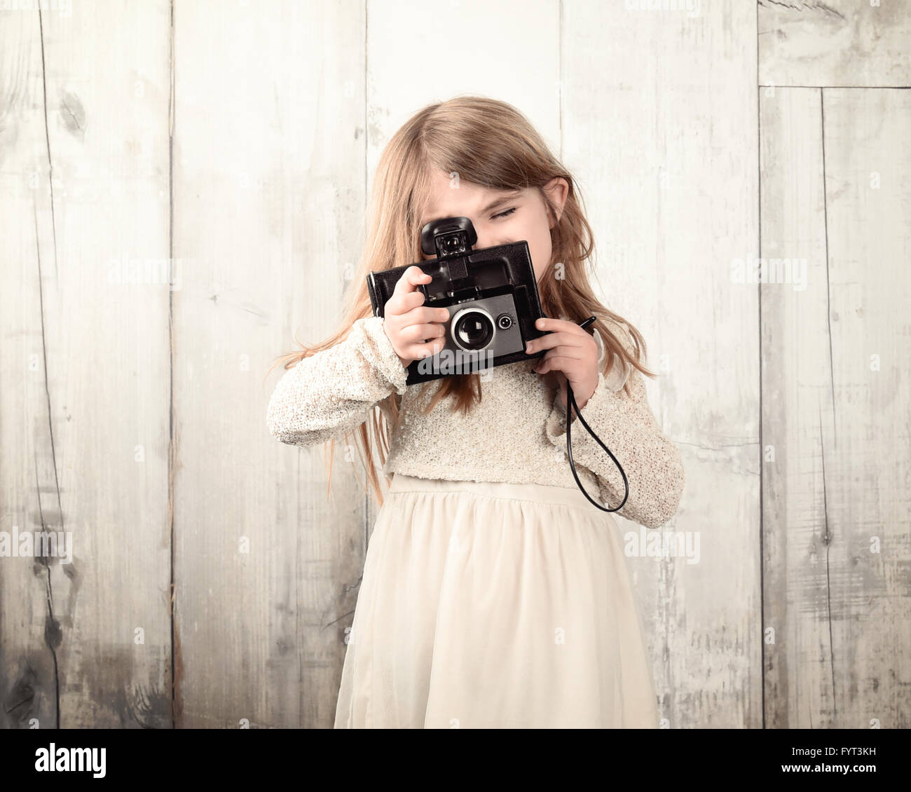 A child photographer is taking a photo with an old film camera against a white wood wall for an art or creativity - Stock Image