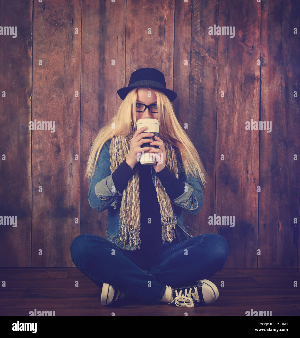 A young hipster woman is drinking a coffee drink against a wood background. She has glasses and a hat on. - Stock Image