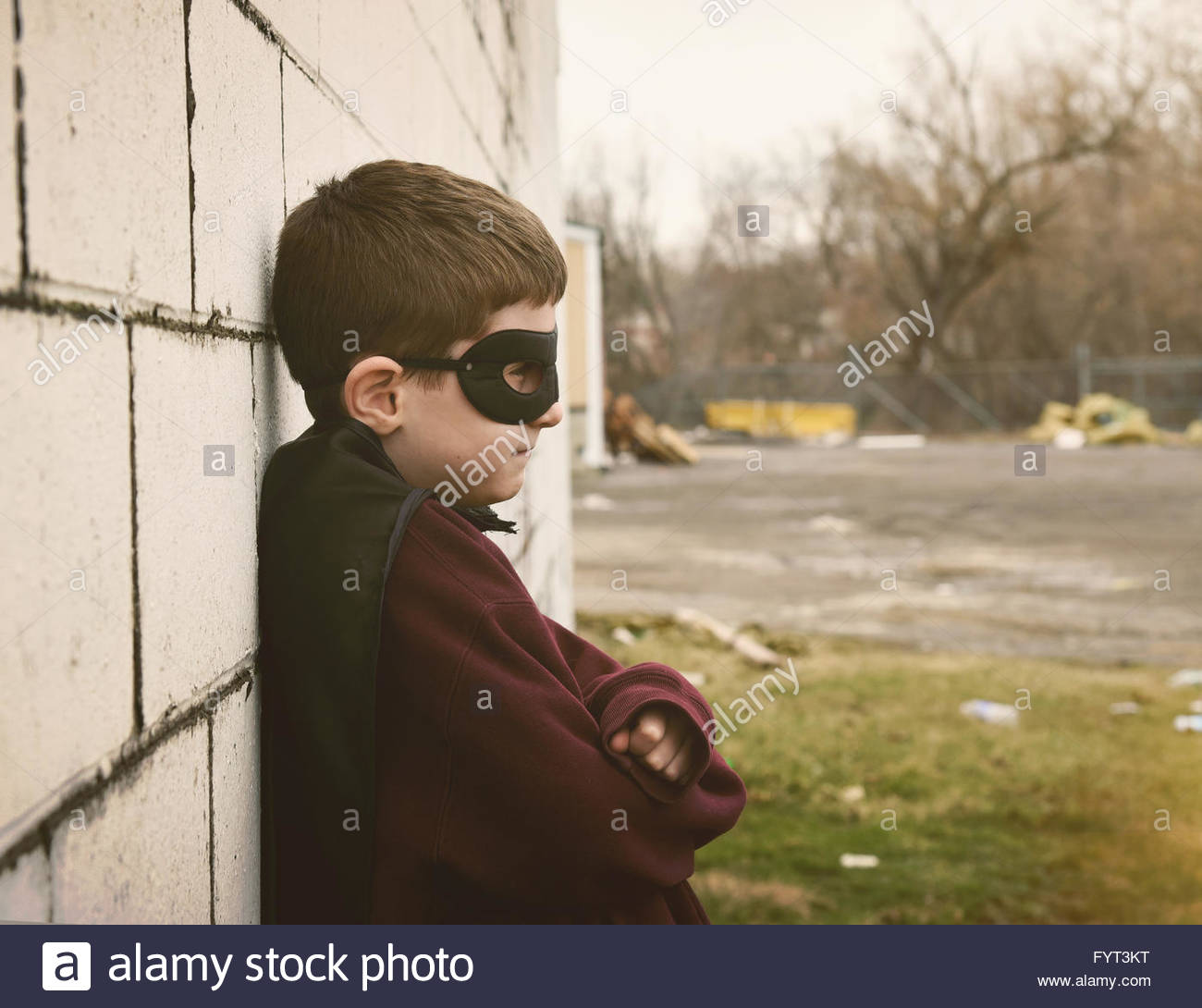 A young boy is dressed as a super hero against a wall with a city fence and pollution for an environment or safety - Stock Image