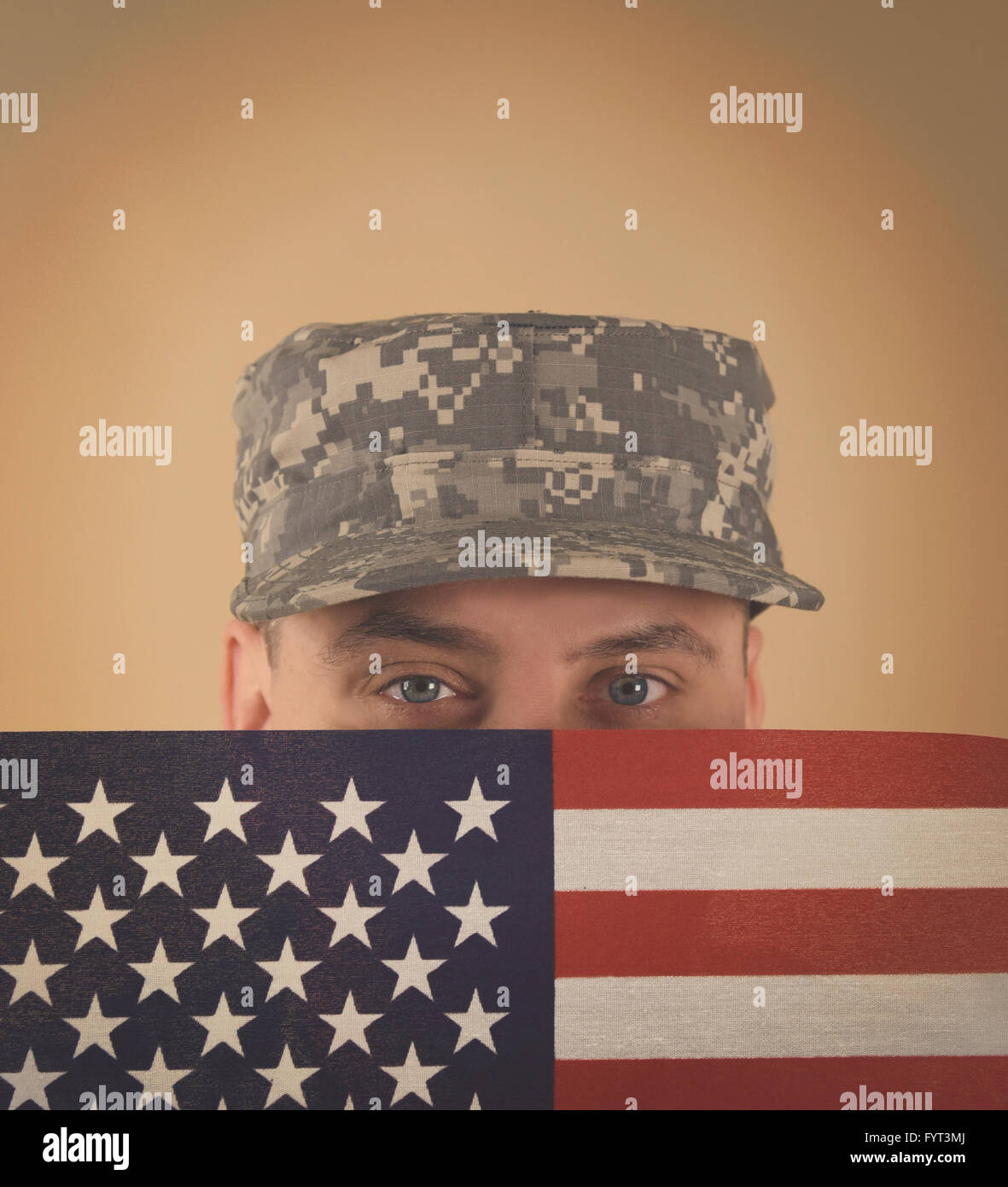 A military army soldier is holding an American flag up to his face with a uniform on and copyspace for a veteran, - Stock Image