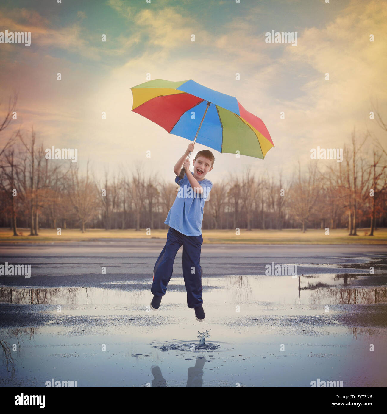 A boy is jumping high in the air up to the sky with a rainbow umbrella and a rain puddle with a splash of water - Stock Image