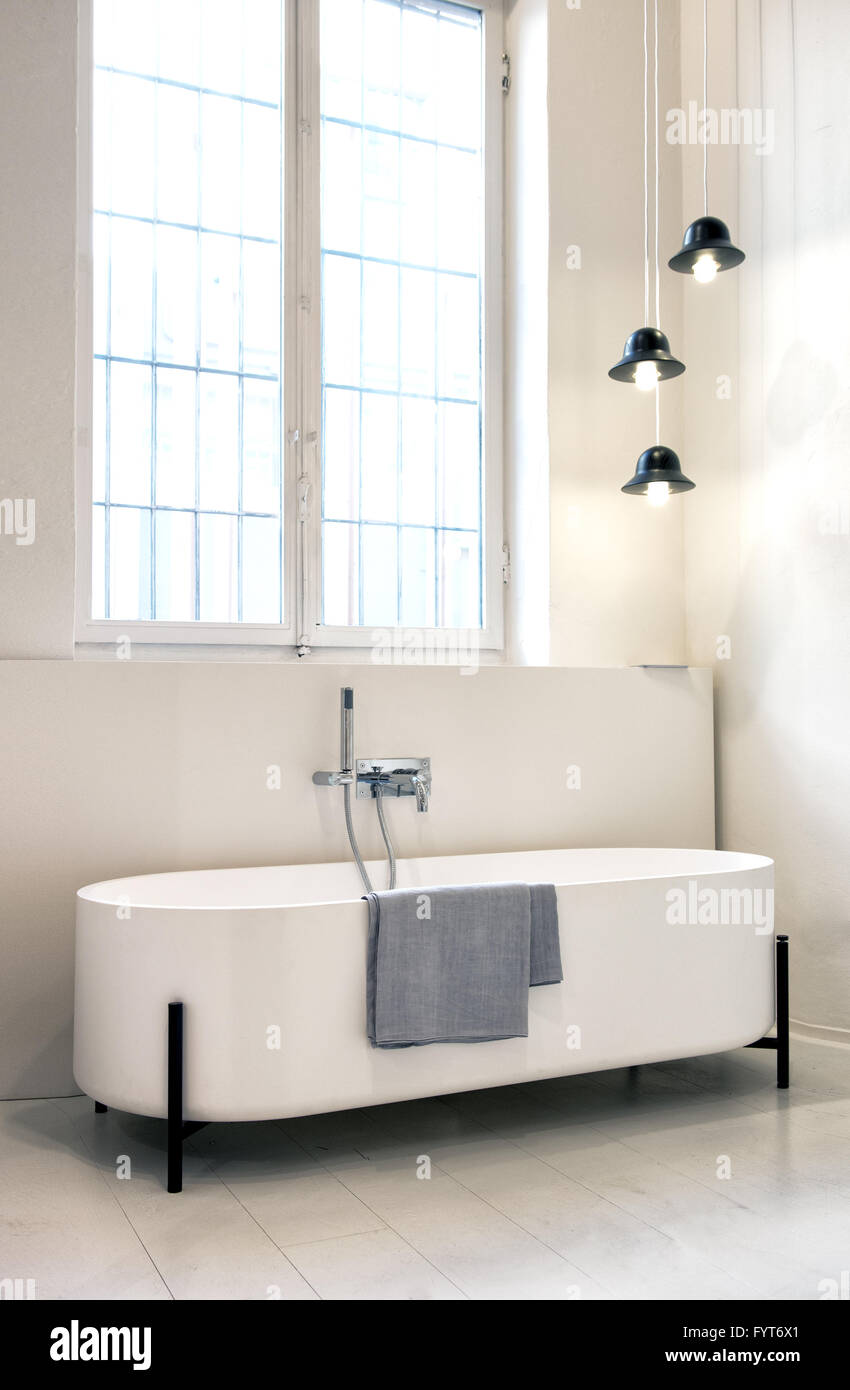 Modern Freestanding Designer Bathtub With Oval Curved Ends In A Monochrome  White Bathroom Interior With Small