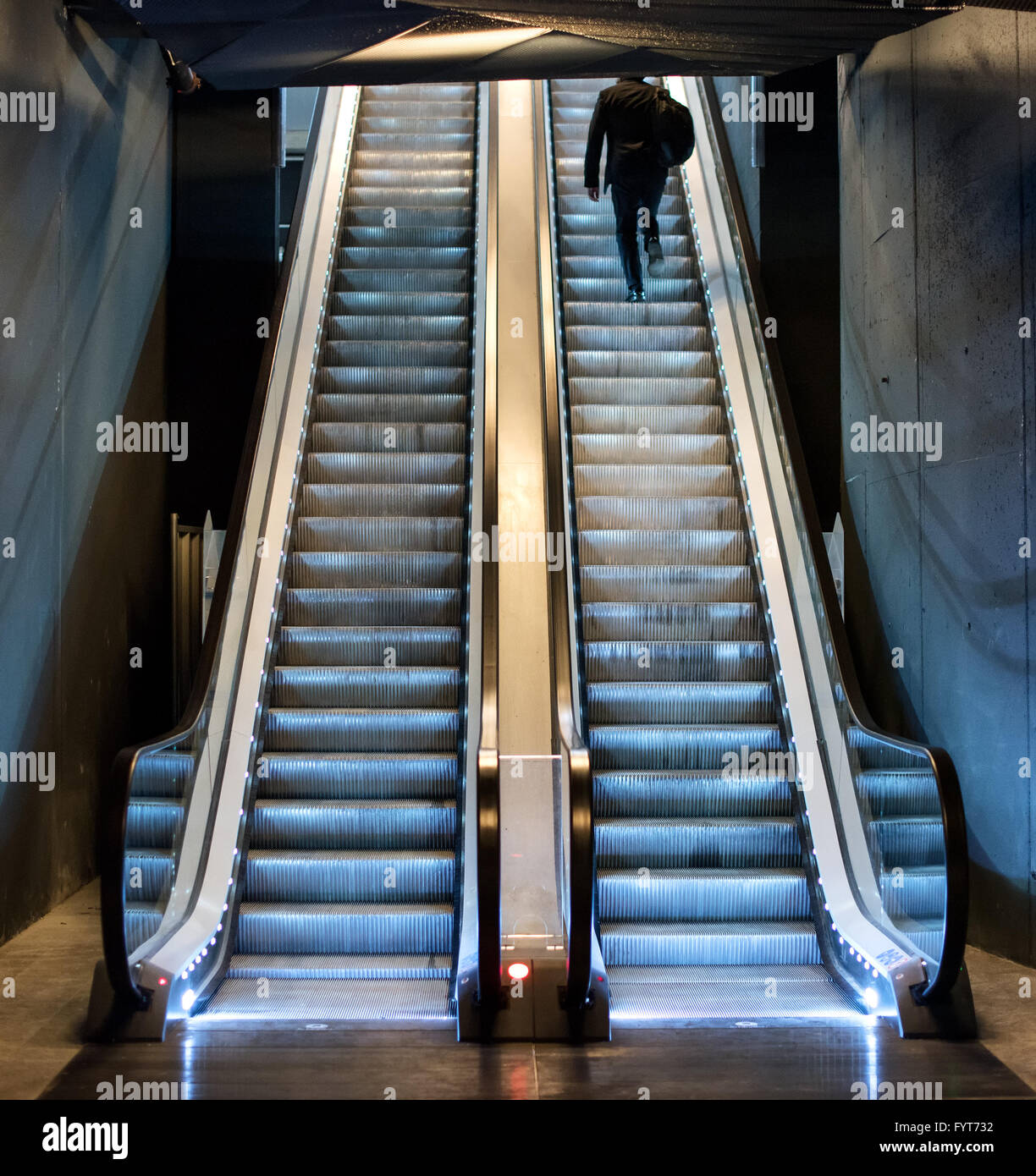 Man ascending an escalator from a subway riding up the moving treads towards daylight at the top, view from the - Stock Image
