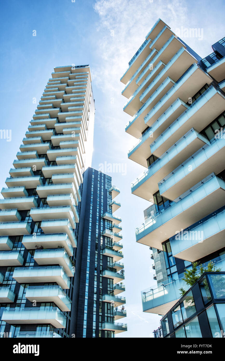 Low angle wide view of tall residential apartment building with staggered balconies in Milan Italy - Stock Image
