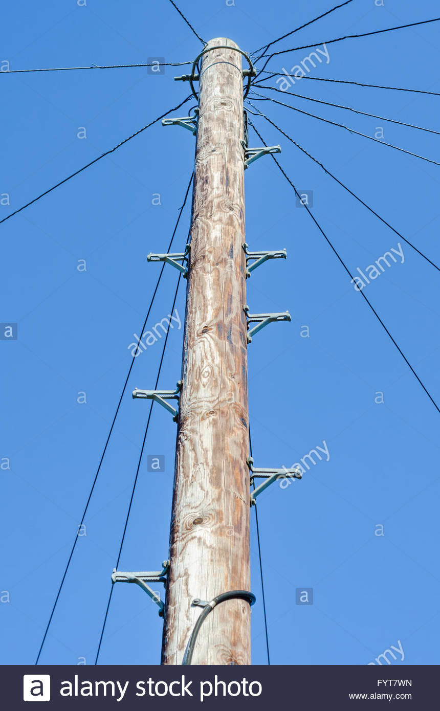 Wooden telegraph pole against blue sky. - Stock Image