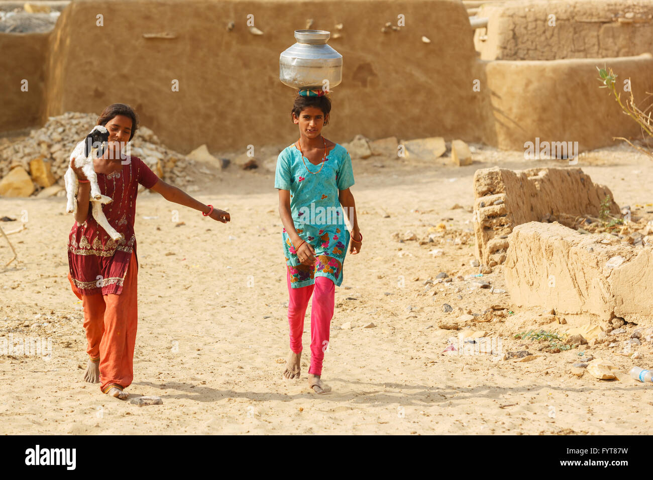women and children draw water from the draw well and carry