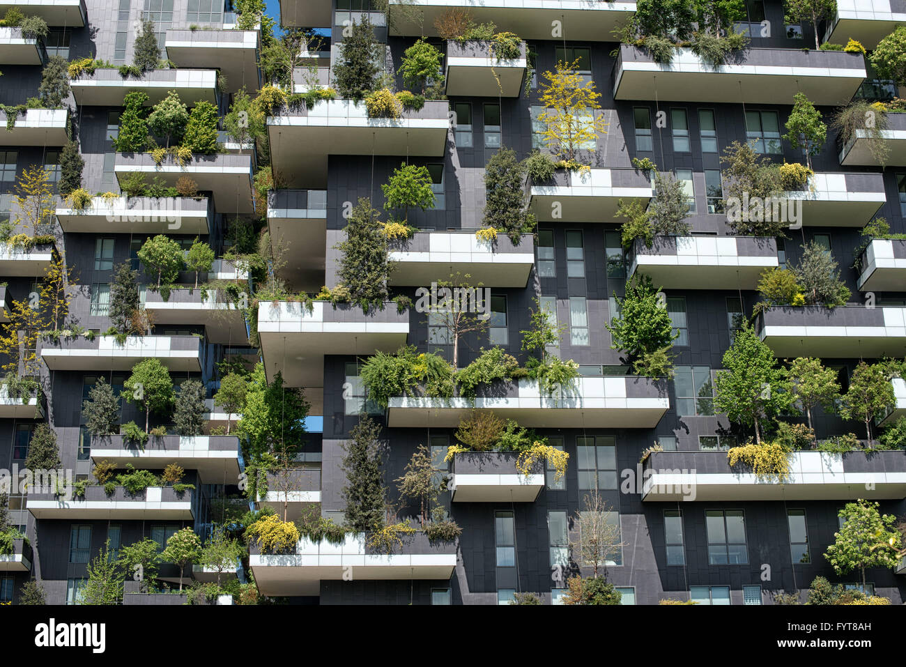 Tight detail view on trees and shrubs on vertical forest apartment building in downtown Milan, Italy - Stock Image