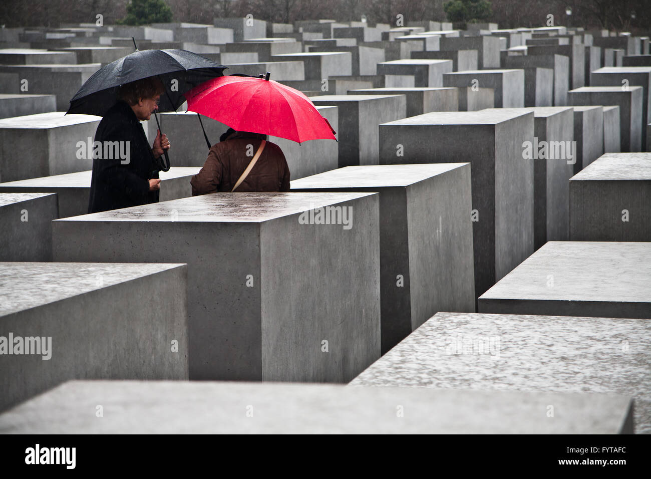 Couple sheltering under black and red umbrellas at the Memorial to the murdered Jews of Europe in Berlin, Germany. - Stock Image