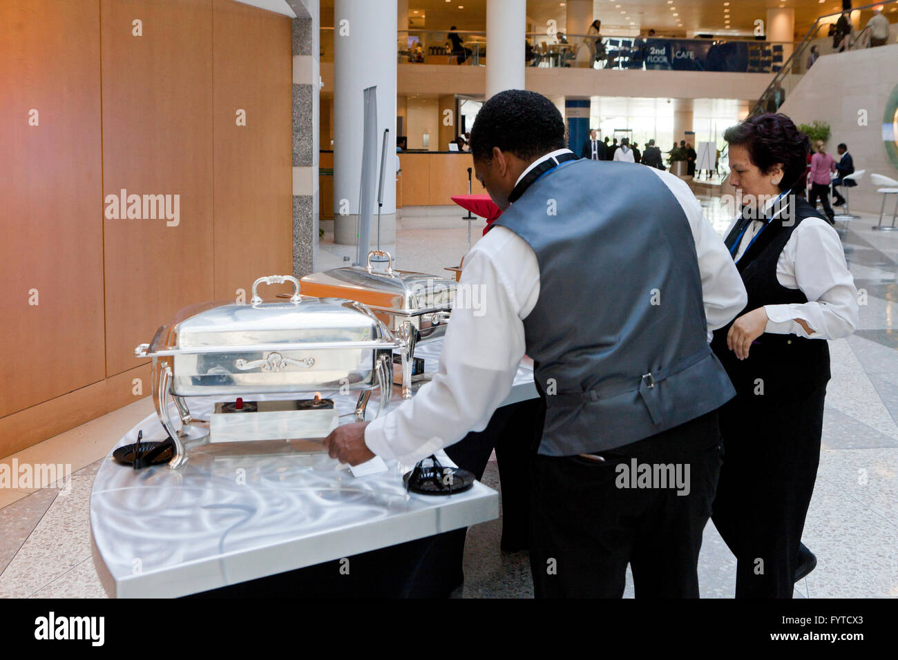 Lounge server preparing chafers of food for guests - USA - Stock Image