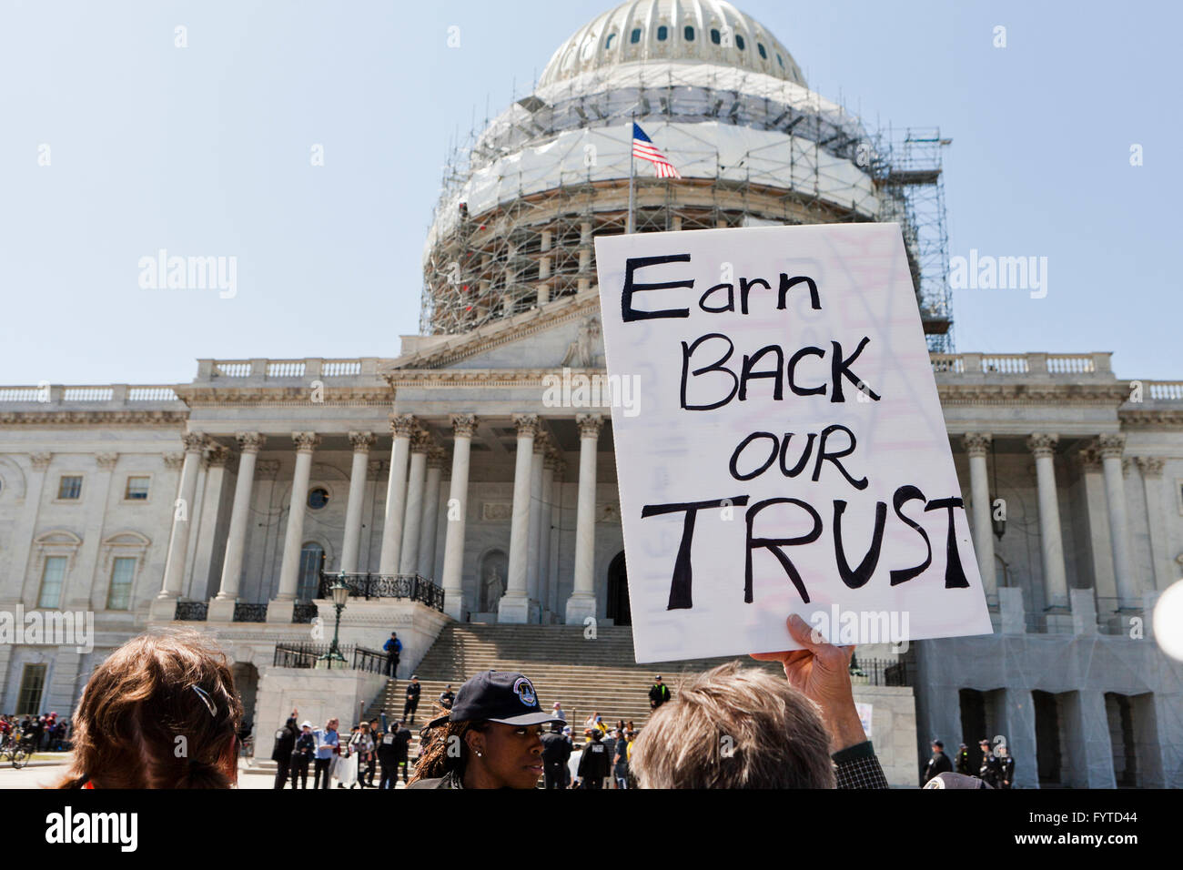 Progressive activist holding 'Earn Back Our Trust' sign in front of the US Capitol building - April 13, - Stock Image