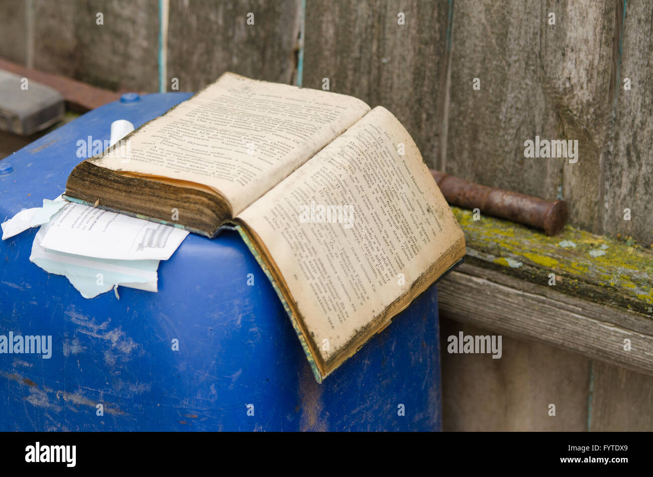 An old book lies in the barrel of the fence - Stock Image