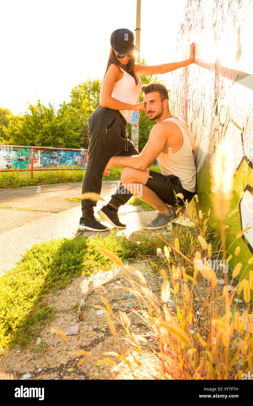 Young Couple standing at a wall in a urban environment - Stock Image