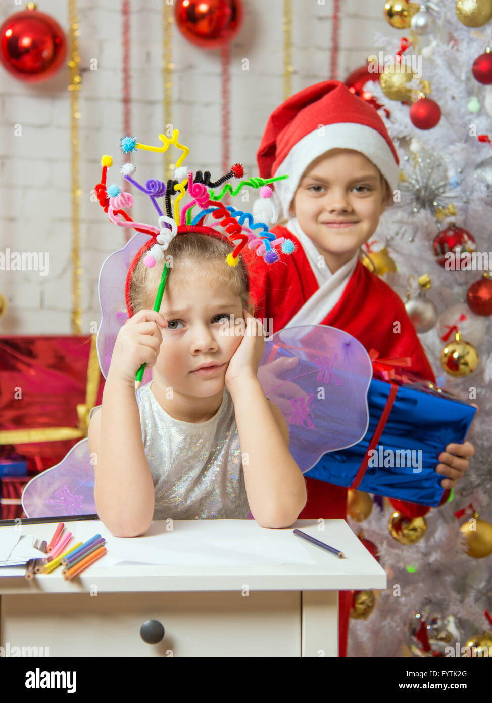 Girl sits at a table with fireworks on the head, santa claus her ready to give her a gift - Stock Image