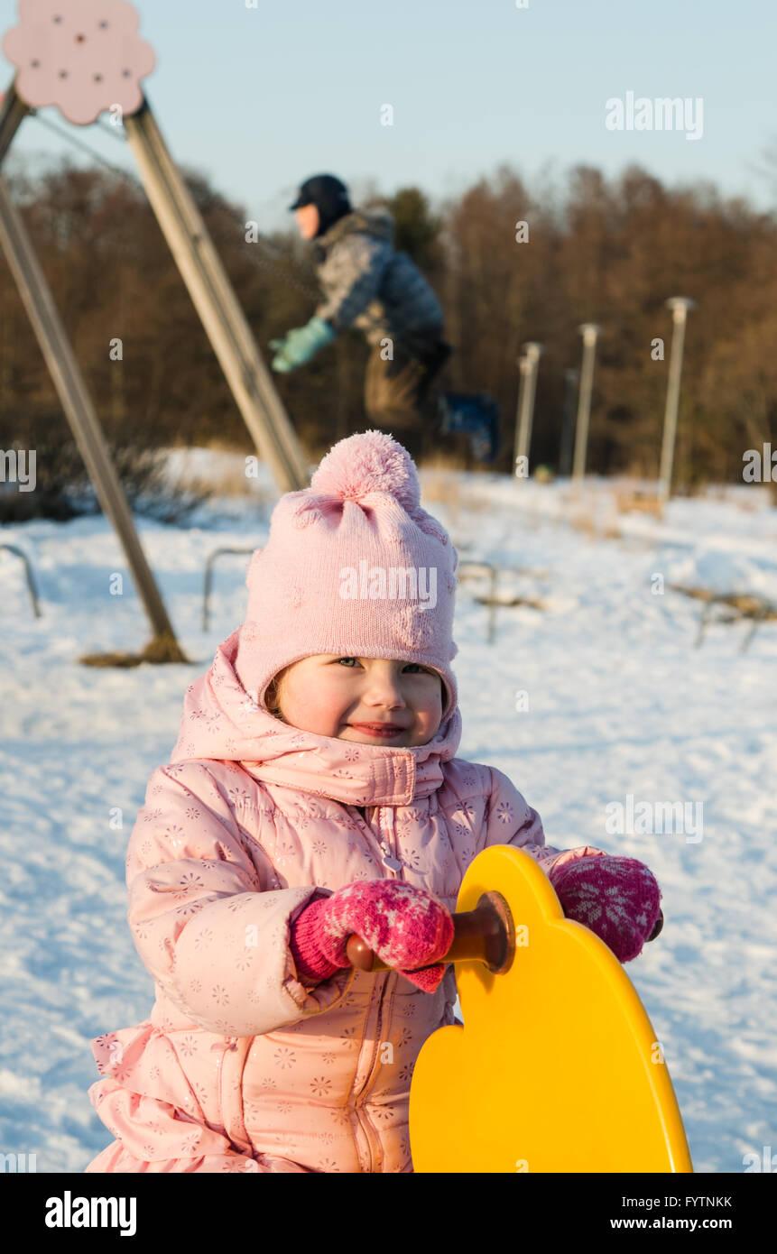 Children swinging on a swing in winter - Stock Image