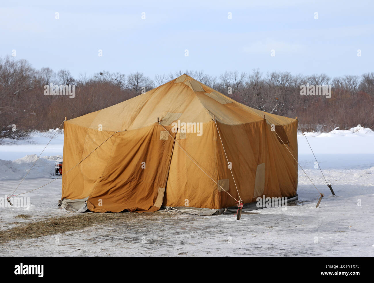 Military khaki tent in the snow polar region in a forest - Stock Image