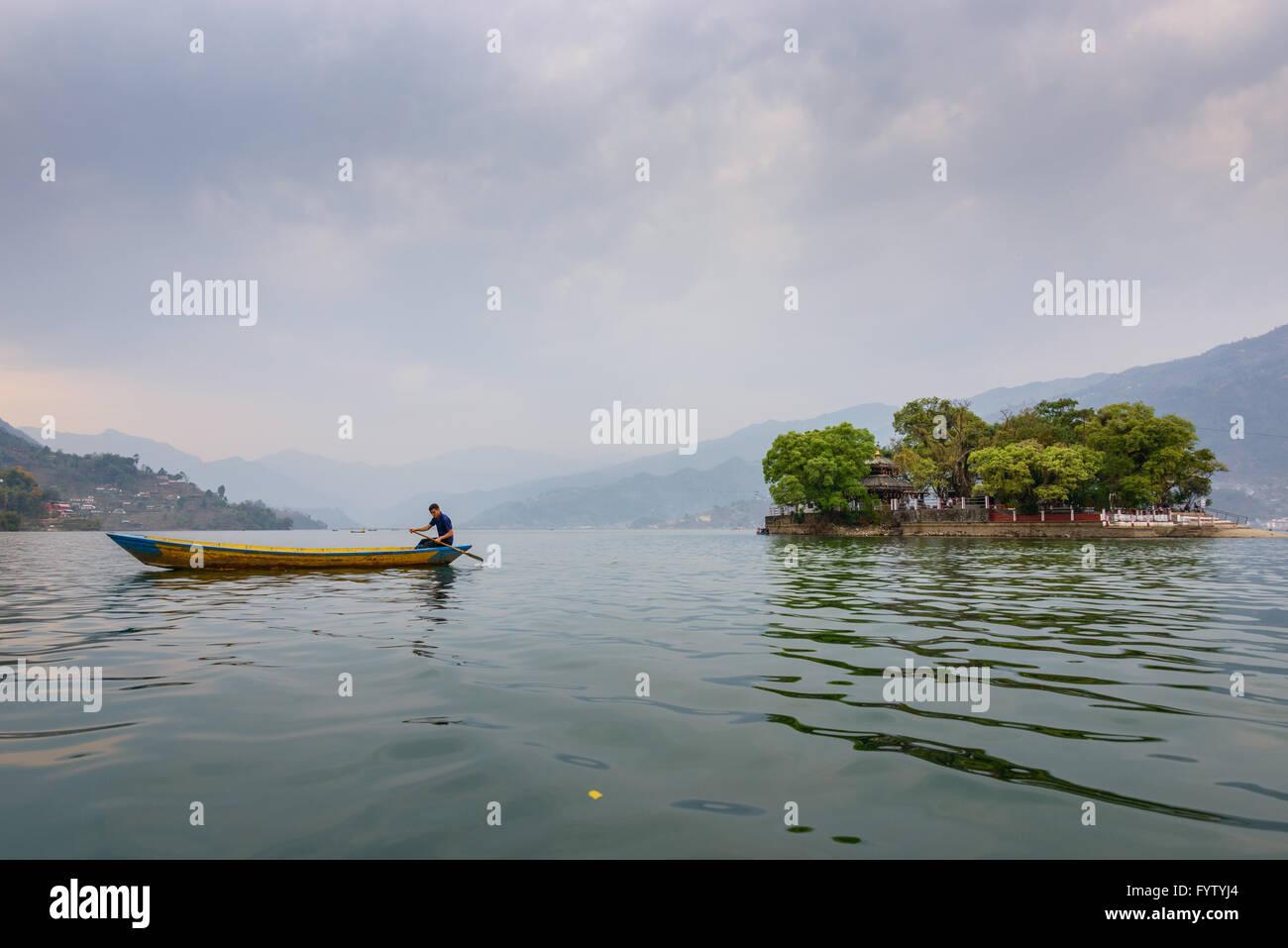 Nepalese man paddling on Phewa Lake in Pokhara, Nepal - Stock Image